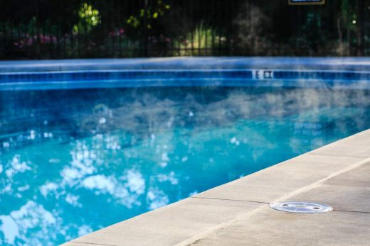 Steam,Rising,From,Heated,Swimming,Pool,With,Concrete,Deck